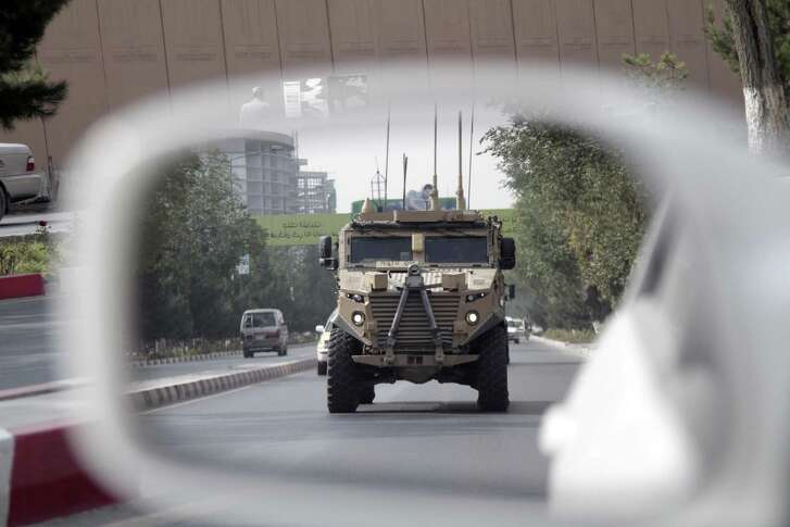 """A patrolling U.S. armored vehicle is reflected in the mirror of a car in Kabul, Afghanistan, Wednesday, Aug. 23, 2017.  In a national address Monday night, U.S. President Donald Trump reversed his past calls for a speedy exit and recommitted the United States to the 16-year-old conflict, saying U.S. troops must """"fight to win."""" (AP Photo/Rahmat Gul)"""