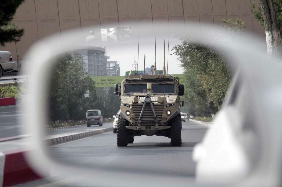 """A patrolling U.S. armored vehicle is reflected in the mirror of a car in Kabul, Afghanistan, Wednesday, Aug. 23, 2017.  In a national address Monday night, U.S. President Donald Trump reversed his past calls for a speedy exit and recommitted the United States to the 16-year-old conflict, saying U.S. troops must """"fight to win."""" (AP Photo/Rahmat Gul) Photo: Rahmat Gul, STF / Associated Press / Copyright 2017 The Associated Press. All rights reserved."""