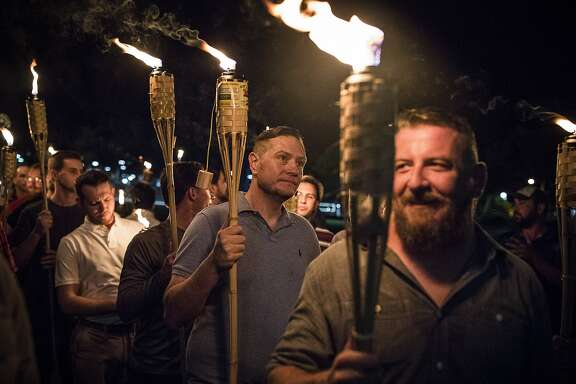 "FILE — A torch-lit march by white nationalists through the grounds of the University of Virginia in Charlottesville, Va., Aug. 11, 2017. Lamplight Farms, whose Tiki torches were used by white nationalist protesters, said ""We do not support their message or the use of our products in this way."" (Edu Bayer/The New York Times)"