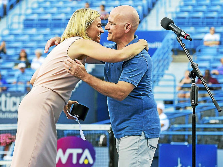 (Peter Hvizdak / Hearst Connecticut Media)   New Haven,Connecticut: Tuesday, August 22, 2017.   Connecticut Open tennis tournament director Anne Worcester, left, hugs Hartford Courant sports reporter Paul Doyle Monday evening on the Stadium Court of the Connecticut Tennis Center in New Haven after Doyle received the 2017 Connecticut Open Dave Solomon Media Award. / New Haven Register