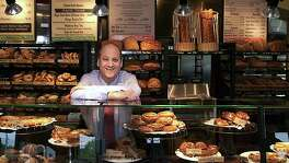 FILE - In this May 2002 file photo, Panera Bread Co. CEO Ron Shaich stands behind a counter at a location in St. Louis. Shaich, who recently sold the cafe chain he founded for $7.2 billion, says that a Wall Street culture relentlessly focused on short-term profit and quarterly metrics is stifling innovation.
