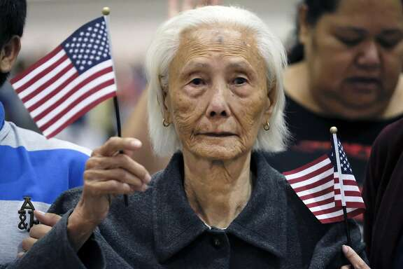Hong Inh waves an American flag as she takes the oath to become a United States citizen at the Los Angeles Convention Center, Tuesday, Aug. 22, 2017. At 103, the Cambodian woman was the oldest of more than 10,000 people who took the oath of allegiance. Three generations of her family were with her, including her 80-year-old daughter and teenage great-granddaughters. (AP Photo/Richard Vogel)