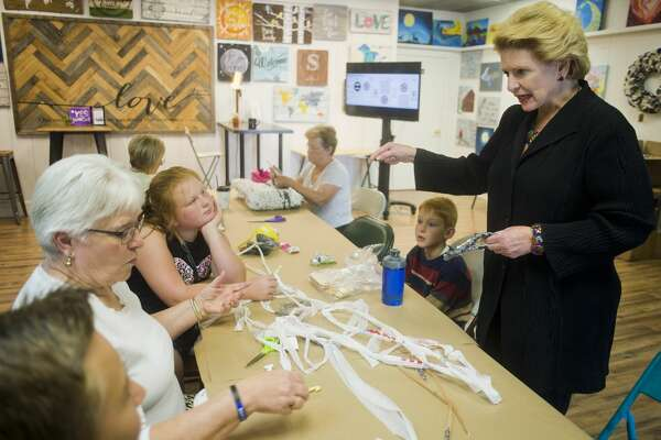 U.S. Sen. Debbie Stabenow chats with a summer camp group as they work on a craft at Live Oak Coffeehouse during an afternoon of visiting small businesses in Midland on Wednesday, August 23, 2017.