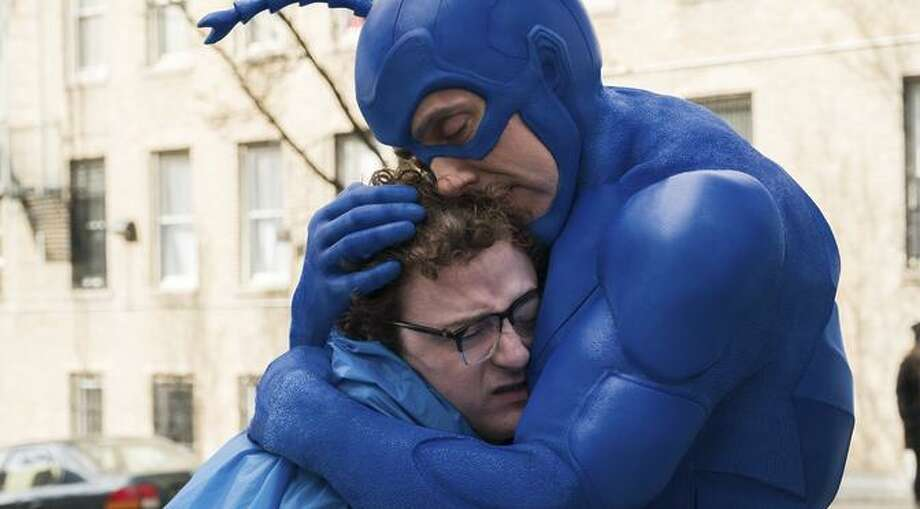 The Tick (Peter Sera finowicz) embraces accountant Arthur (Griffin Newman), whom he helps become a superhero. Photo: Jessica Miglio