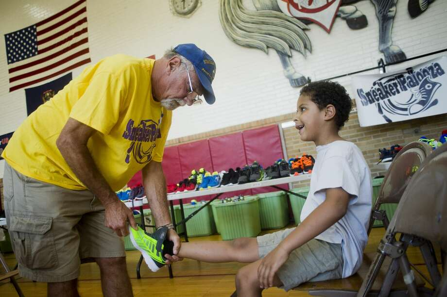 Aiden Tobias, 6, tries on a fresh pair of sneakers with the help of Barry Schihl during the fourth annual Sneakerpalooza, an event which provides thousands of Midland County students in kindergarten through 12th grades a chance to receive brand new, brand name, free athletic shoes, on Tuesday, August 22, 2017 at Carpenter Street School. Another giveaway is scheduled for 4 to 7 p.m. on Aug. 26 at the Beaverton Activity Center. Photo: (Katy Kildee/kkildee@mdn.net)