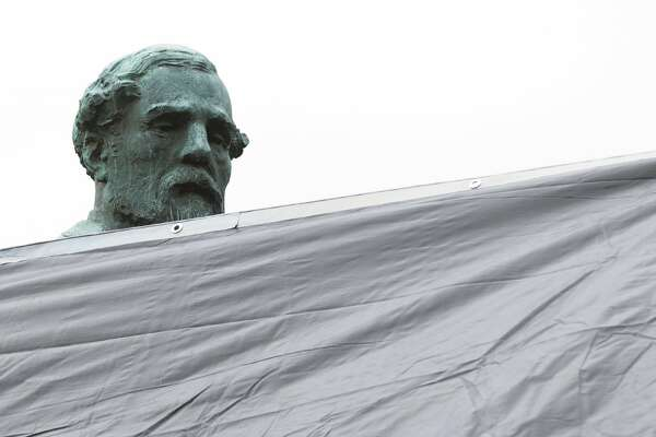 City workers drape a tarp over the statue of Confederate General Robert E. Lee in Emancipation park in Charlottesville, Va., Wednesday, Aug. 23, 2017. The move to cover the statues is intended to symbolize the city's mourning for Heather Heyer, killed while protesting a white nationalist rally earlier this month.  (AP Photo/Steve Helber)