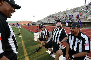 Eighteen-year veteran referee Ronnie Shilo jokes with (from left) Joe Flores, Ryan Moran, and Robert Spain as he reviews procedures and foul calls with his four-man crew (including Chad Lemoine) as they await the start of Friday's scrimmage between West Orange - Stark and Port Neches - Groves at Port Neches. Area teams will have enough referees to work games throughout this season, but just barely as the numbers have dwindled. A combination of low pay and long hours, coupled with a decline in younger generations advancing to replace retiring refs   has led to the shortage.  Photo taken Friday, August 18, 2017 Kim Brent/The Enterprise