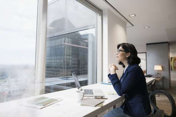 Pensive businesswoman at laptop looking out urban office window Details Credit: Hero Images Creative #: 681886715