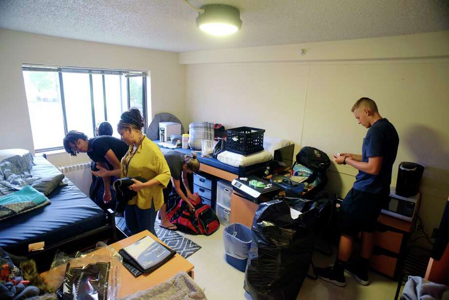 College of Saint Rose freshman Richard Jimenez, left, from the Bronx and his mother, Josefina Cornelio, along with freshman Eric Szillus, far right, from North Massapequa and his mother, Margie Szillus, set up their room as freshmen moved into their housing on Wednesday, Aug. 23, 2017, in Albany, N.Y.   (Paul Buckowski / Times Union) Photo: PAUL BUCKOWSKI, Albany Times Union / 20041333A