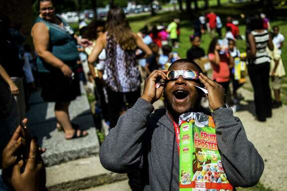 Drop-off points for used glasses will include astronomy clubs, schools, libraries, optical shops, even businesses unrelated to astronomy. Here, TyRon Robertson, a physical activity coordinator at Freeman Elementary School, reacts to witnessing his first solar eclipse in Flint, Michigan.