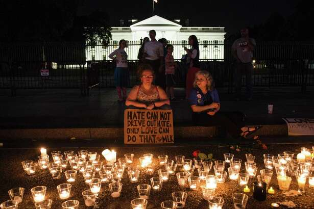Gathering in front of the White House on August 13, people hold a candlelight vigil after the death of a counter-protestor in a violent rally in Charlottesville, Virginia. Readers address the racial turmoil in the nation.