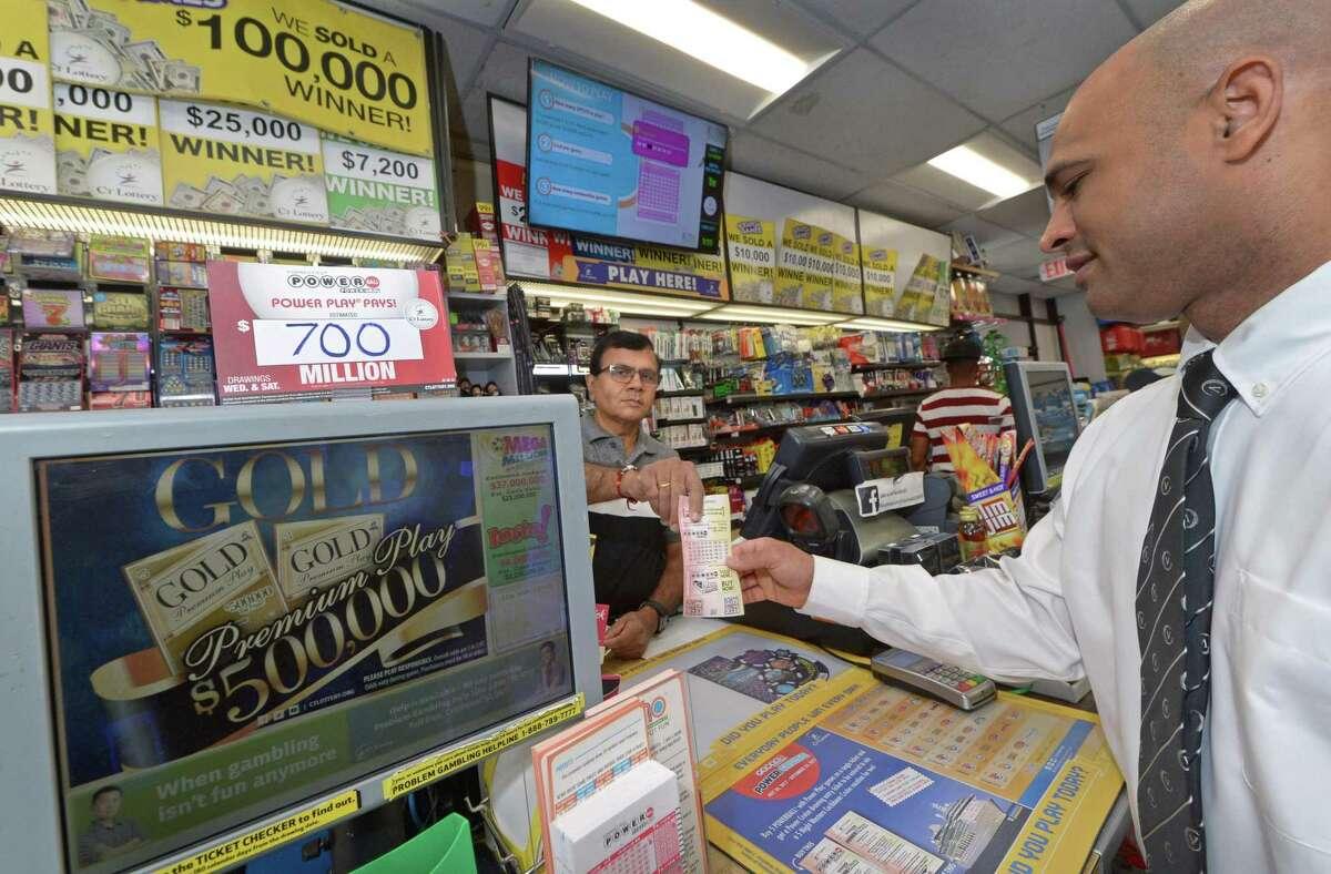 Proprietor Upen Shah sells Powerball lottery tickets to Juan Juma at Crossroads Variety on Connecticut Avenue on Wednesday.