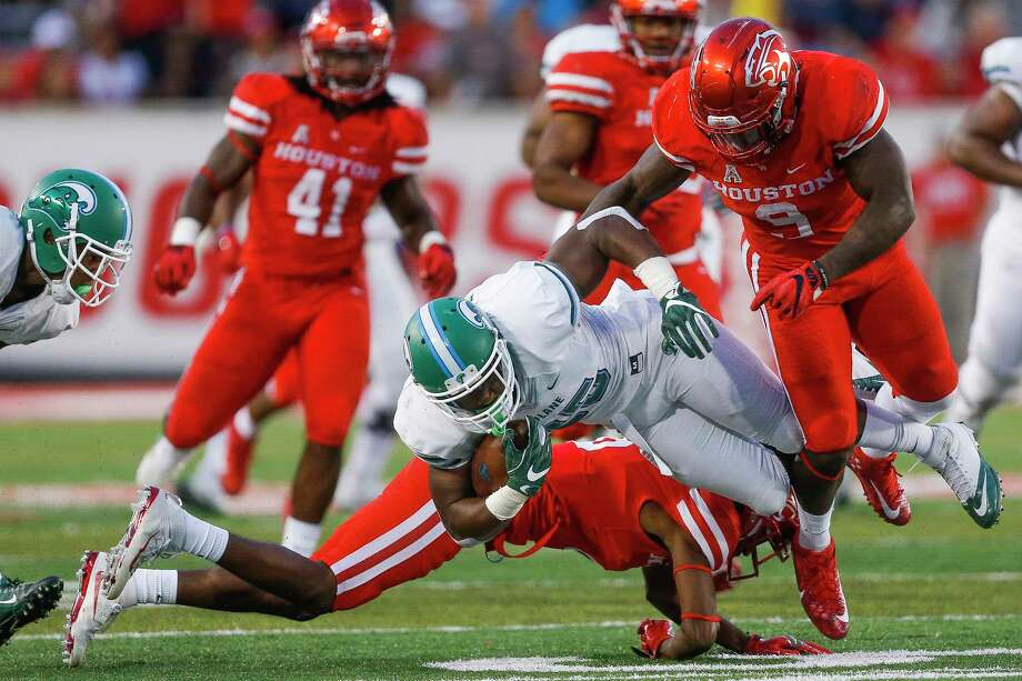 """UH linebacker Matthew Adams, right, here getting in on the action against Tulane last year, is projected as the vocal leader, team captain material and """"rock of the defense"""" heading into this season. Photo: Michael Ciaglo, Staff / © 2016  Houston Chronicle"""
