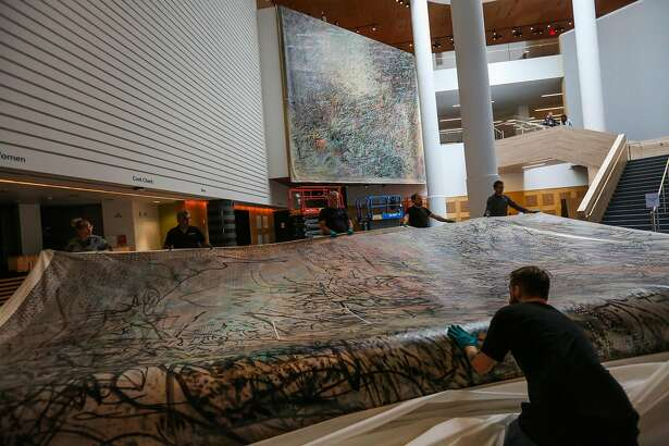 Art installers unload the second piece of a two part mural done by artist Jill Mehretu at the MOMA in San Francisco, Calif., on Wednesday, Aug. 23, 2017.
