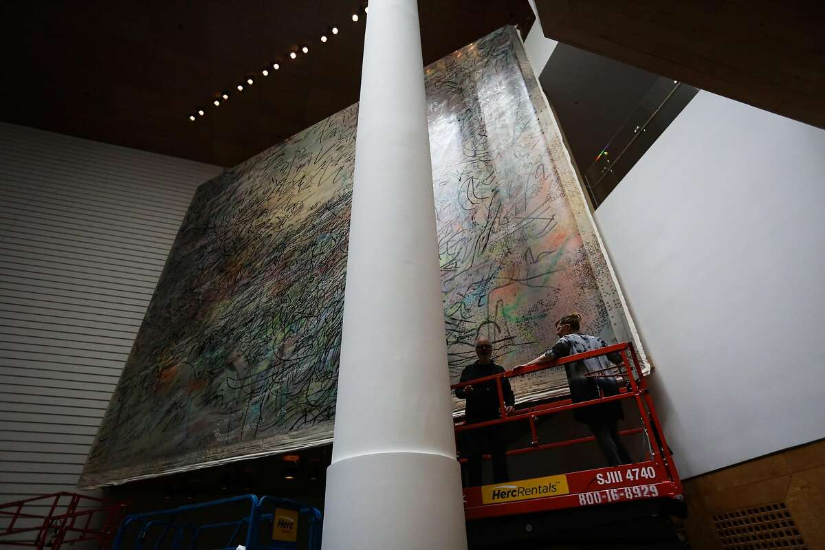 Sarah Rentz and Kent Roberts (left) check up on a mural that was installed earlier that morning by artist Jill Mehretu at the MOMA in San Francisco, Calif., on Wednesday, Aug. 23, 2017.