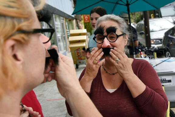 Isobel White tries on her Groucho Marx disguises with friends after purchasing them at Mr. Mopps' Toy Shop in Berkeley, CA, on Wednesday August 23, 2017. Isobel and friends plan on wearing the Groucho Marx glasses and mustaches while counter protesting at the upcoming right wing �No to Marxism� rally in Berkeley.