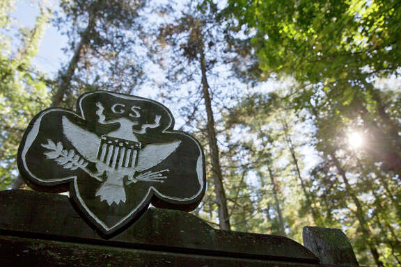 FILE - This Monday, Sept. 22, 2014 file photo shows the official Girl Scouts crest at the entrance of a Girl Scout Camp in Lapeer, Mich. As of March 2017, GSUSA reported 1,566,671 youth members and 749,008 adult members — down from just over 2 million youth members and about 800,000 adult members in 2014. (Erin Kirkland/The Flint Journal-MLive.com via AP)
