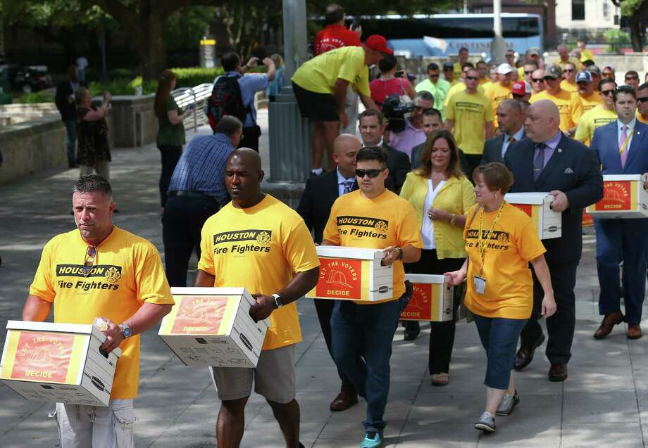 Houston firefighters carry boxes, filled with more than 32,000 signatures to put equal pay on the ballot, over to the City Hall Annex building last month.  ( Godofredo A. Vasquez / Houston Chronicle ) Photo: Godofredo A. Vasquez, Staff / The Advocate