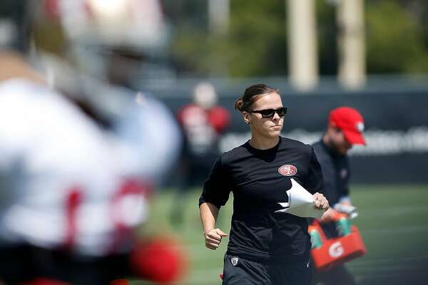 San Francisco 49ers assistant coach Katie Sowers players run through drills during practice at the San Francisco 49ers training facility on Wednesday, August 23, 2017, in Santa Clara, California. Sowers, 31, made more history, becoming the NFL's first openly gay coach. San Francisco 49ers officially hired Katie Sowers for the 2017 season last week, making her the team's first female assistant coach.