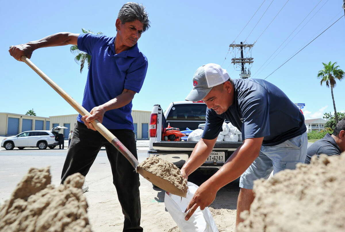 Leo Sermiento, left, and Emilio Gutierrez, right, fill sandbags in preparation of a tropical system on Wednesday, Aug. 23, 2017, on South Padre Island