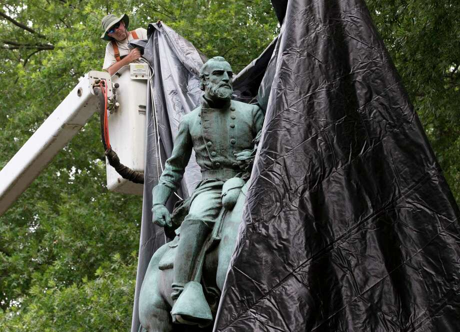 City workers drop a tarp over the statue of Confederate General Stonewall Jackson in Justice park in Charlottesville, Va., on Wednesday. Some residents cheered as the statue was covered, but later one man began cutting the tarp. Photo: Steve Helber, STF / Copyright 2017 The Associated Press. All rights reserved.