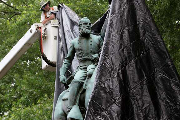 City workers drop a tarp over the statue of Confederate General Stonewall Jackson in Justice park in Charlottesville, Va., on Wednesday. Some residents cheered as the statue was covered, but later one man began cutting the tarp.