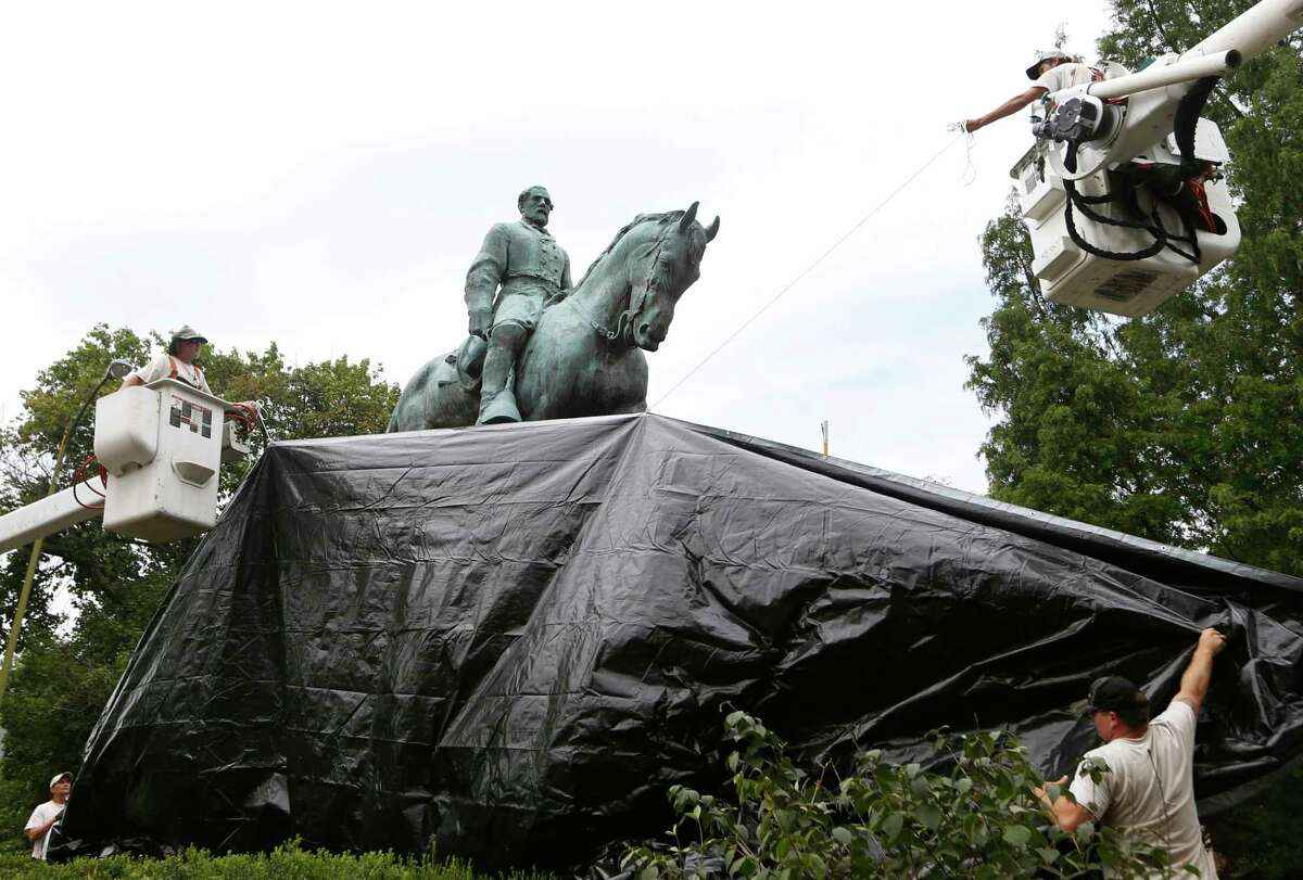 City workers drape a tarp over the statue of Confederate General Robert E. Lee in Emancipation park in Charlottesville, Va., last year. In the city of Tyler, school board trustees left alone a school named after him.  (AP Photo/Steve Helber)
