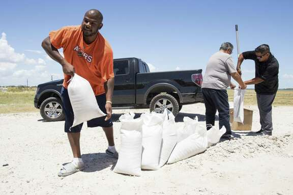 Anthony Rayford and Alma Longbotham fill a sandbag behind the Seaman's Memorial Tower in Aransas Pass, Texas, ahead of a tropical storm on Wednesday, Aug. 23, 2017. Texas Gov. Greg Abbott has ordered the State Operations Center to elevate its readiness level and is making state resources available for preparation and possible rescue and recovery actions amid forecasts a tropical storm will make landfall along the Texas Gulf Coast. (Courtney Sacco/Corpus Christi Caller-Times via AP)
