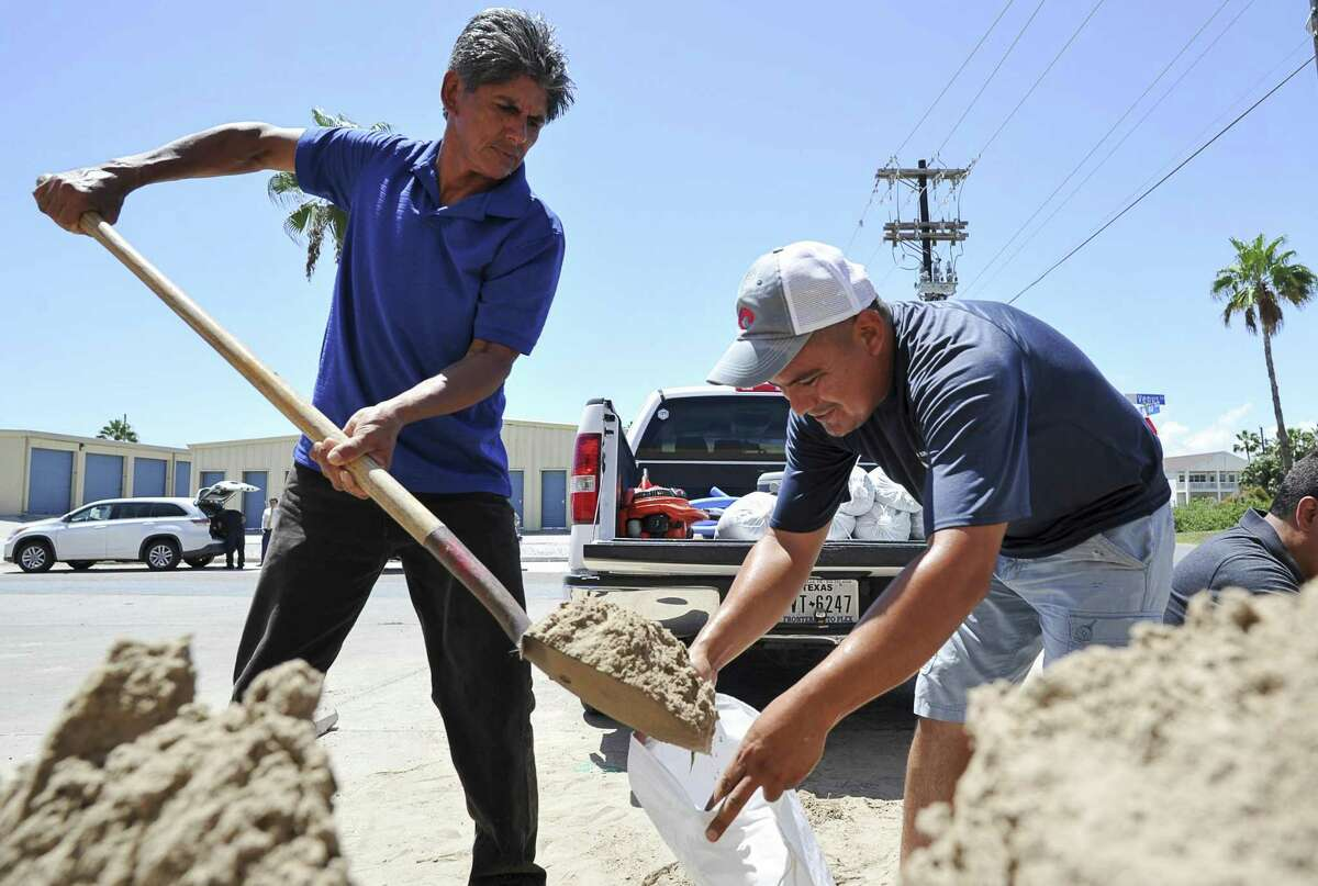 Leo Sermiento, left, and Emilio Gutierrez, right, fill sandbags in preparation of a tropical system on Wednesday, Aug. 23, 2017, on South Padre Island, Texas. Texas Gov. Greg Abbott has ordered the State Operations Center to elevate its readiness level and is making state resources available for preparation and possible rescue and recovery actions amid forecasts a tropical storm will make landfall along the Texas Gulf Coast. (Jason Hoekema/The Brownsville Herald via AP)