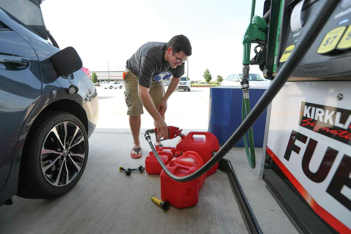 Chris Mathew fills his vehicle and five gas cans at Costco in preparation for Tropical Storm Harvey Wednesday, Aug. 23, 2017, in Pearland. Mathew is an administrator at the Lyndon B. Johnson Hospital and would be required to make it to the hospital is needed.