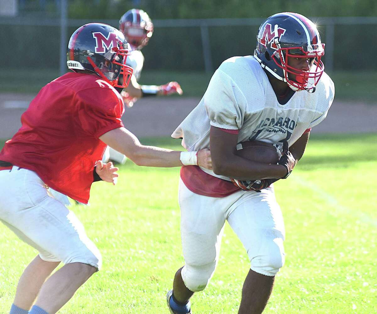 Brien McMahon's Tsai Zoe, right, takes a hand-off from quarterback Tyler Holloran for a long gain while facing Notre Dame-Fairfield in the Wilton Football Jamboree on Wednesday. Seven teams took part in the annual affair.