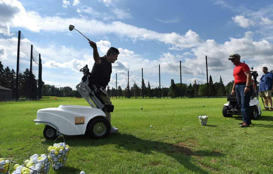 Anthony Netto, founder of the Stand Up & Play Foundation, makes a shot from the driving range with the help of a Paramobile by during an adaptive golf clinic that was hosted by Sunnyview Rehabilitation Hospital at Stadium Golf Course on Wednesday, Aug. 23, 2017, in Schenectady, N.Y. The Paramobile is a specially designed wheelchair that allows its user to stand up. (Will Waldron/Times Union)