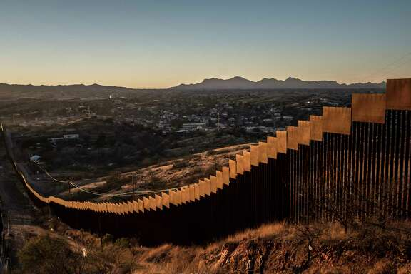 """FILE-- The border wall, here made of tall steel beams in rows, in Nogales. Mexico, Jan. 30, 2017.  Trump at a campaign-style rally in Phoenix on Aug. 22 promised he would shut down the government if Congress does not fund a wall on the southern border. Tuesday's admonition sharpened a suggestion that Trump made early this year, in the wake of a budget agreement he grudgingly accepted even though it omitted money for the wall, that the U.S. needed """"a good 'shutdown'"""" this fall to force a partisan confrontation over federal spending. (Bryan Denton/The New York Times)"""