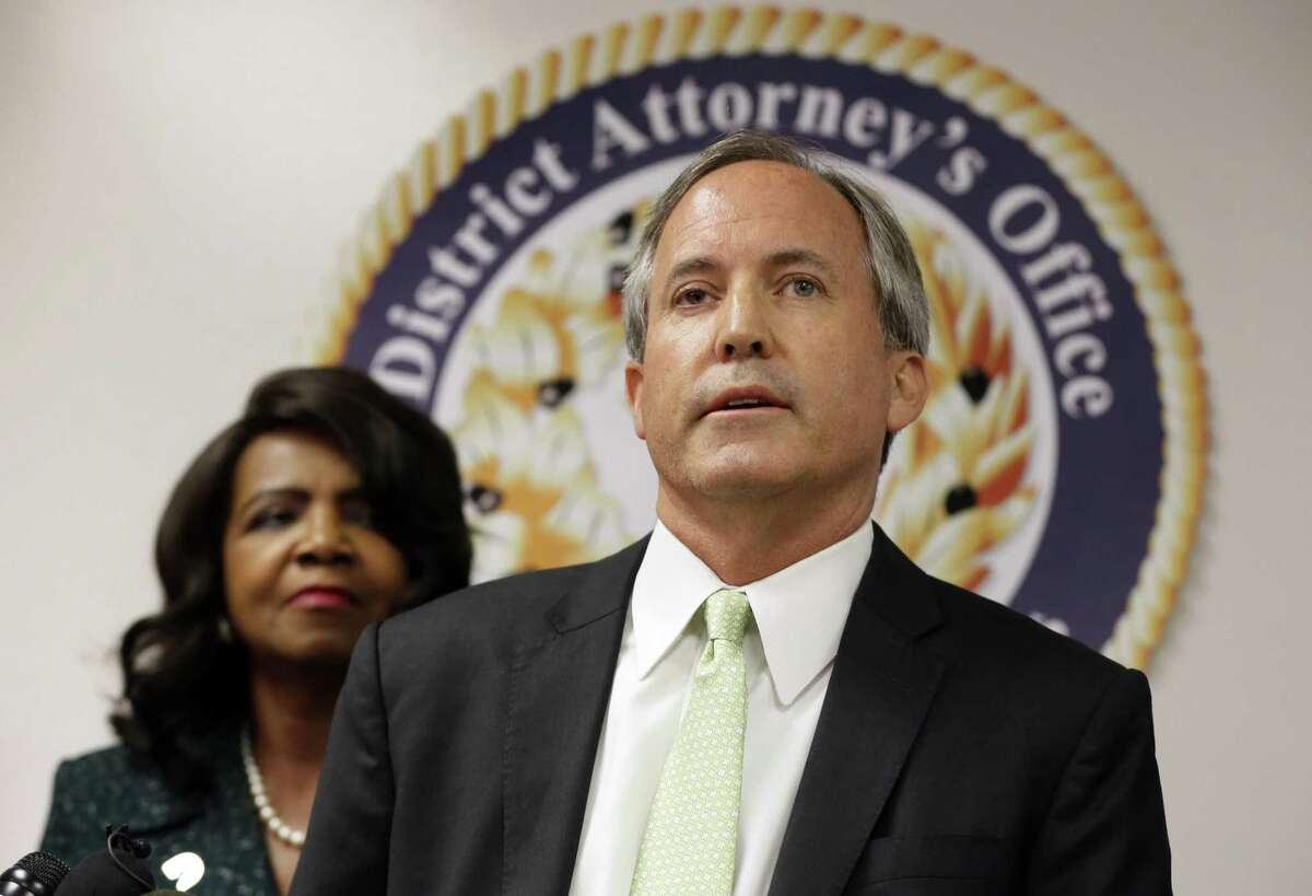 Texas Attorney General Ken Paxton, center, makes comments during a news conference as Dallas County District Attorney Faith Johnson, left, listens, Wednesday, June 22, 2017, in Dallas. A federal judge has tossed out Texas' voter identification law, but attorney general Ken Paxton is already pledging to appeal the ruling.(AP Photo/Tony Gutierrez)
