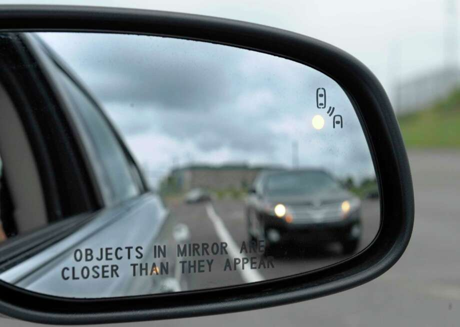 FILE - In his May 22, 2012 file photo, a side mirror warning signal in a Ford Taurus at an automobile testing area in Oxon Hill, Md. Safety systems to prevent cars from drifting into another lane or warn drivers of vehicles in their blind spots are beginning to live up to their potential to significantly reduce crashes, according to two studies released Wednesday, Aug. 23, 2017.  (AP Photo/Susan Walsh, File) Photo: Susan Walsh, STF / Copyright 2017 The Associated Press. All rights reserved.