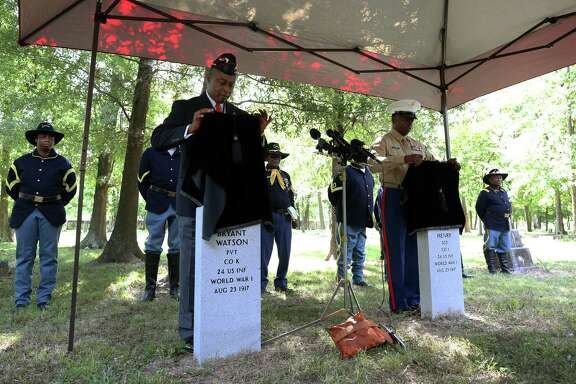 Retired Marine Corps Master Sgt. Nathaniel Broussard, left, and Marine Master Sgt. Eric Stone unveil the tombstones for Army Pvt. Bryant Watson and Sgt. Vida Henry during the 100th Commemoration of the Camp Logan Riot at College Park Cemetery.