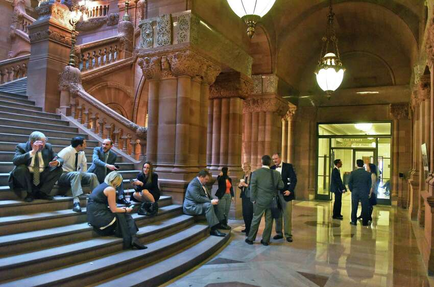 Lobbyists gather on the Capitol's Million Dollar Staircase between the Senate and Assembly as they wait for word on a state budget Friday March 31, 2017 in Albany, NY. (John Carl D'Annibale / Times Union)
