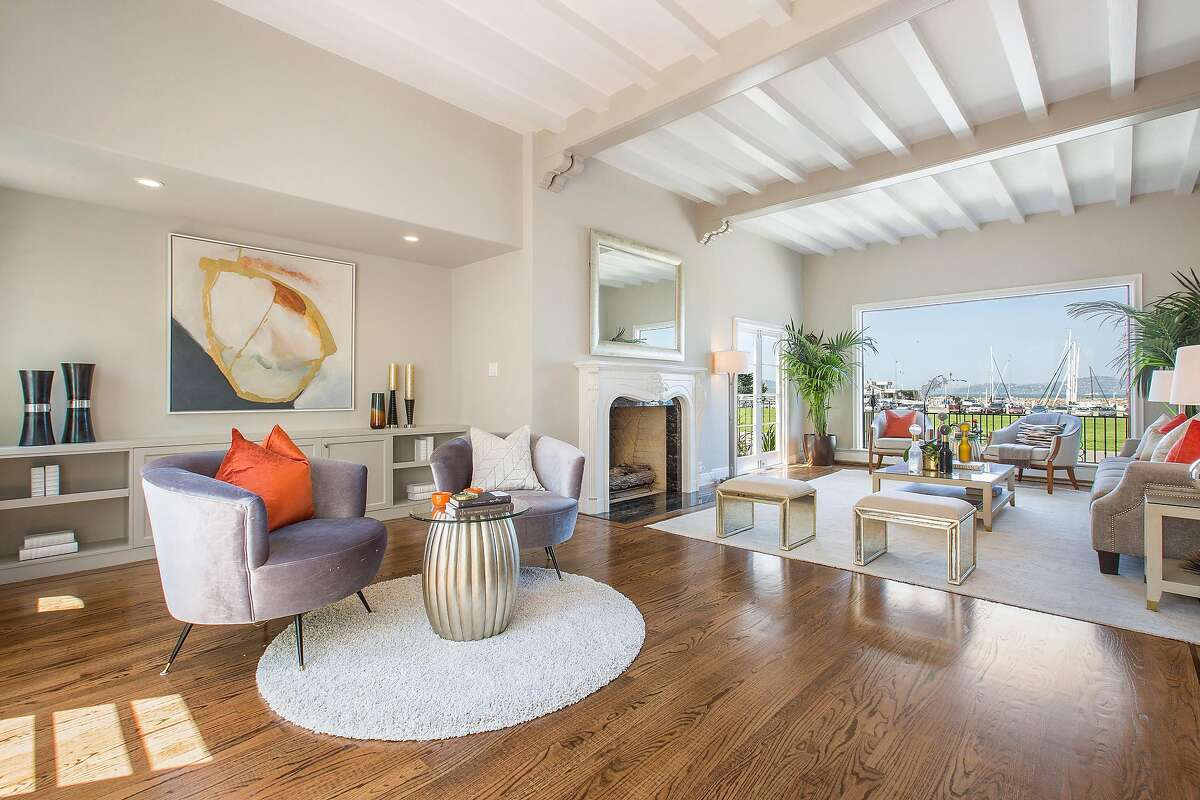 The spacious living room features a fireplace and unobstructed views of the bay and Marina Green.