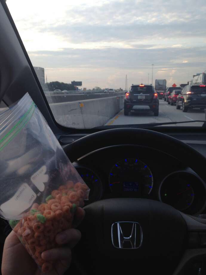 Houston Chronicle reporter Fernando Alfonso eats a bag of cereal while stuck in US-290 traffic on Aug. 24, 2017. Houston Transtar reported a 2-vehicle wreck closed multiple lanes for eastbound motorists near Pinemont Drive. Photo: Fernando Alfonso/Houston Chronicle