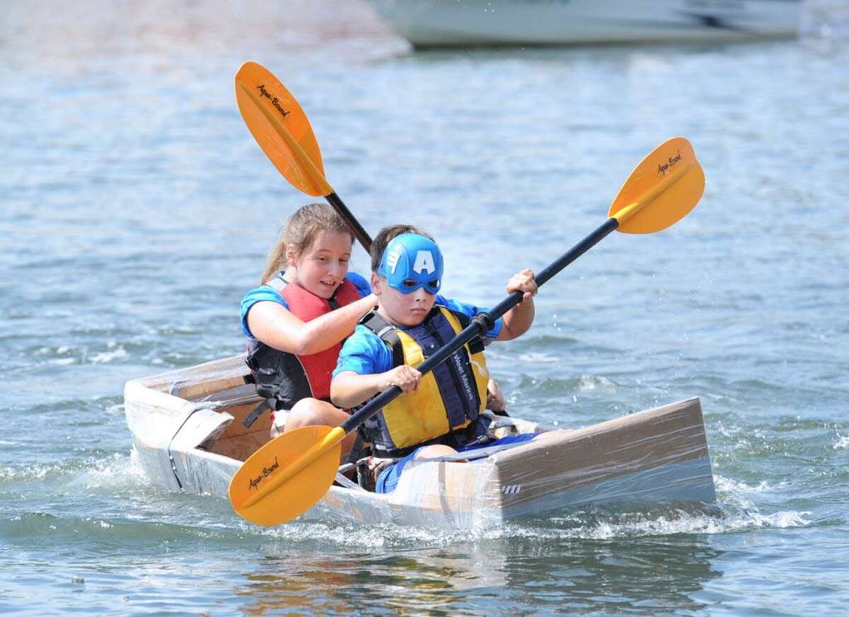 """Cos Cob residents David Zelenz, 11, front, and his siter Marina Zelenz, 12, propel the Captain America kayak during the SoundWaters HarborFest 16 cardboard kayak race on Stamford Harbor off Harbor Point, Stamford, Conn., Saturday, Aug. 27, 2016. The Stamford kayak """"Tribe"""" propelled by the duo of Griffin Gigliotti and Angus Manion took first place in the championship race."""