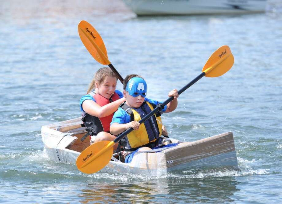 "Cos Cob residents David Zelenz, 11, front, and his siter Marina Zelenz, 12, propel the Captain America kayak during the SoundWaters HarborFest 16 cardboard kayak race on Stamford Harbor off Harbor Point, Stamford, Conn., Saturday, Aug. 27, 2016. The Stamford kayak ""Tribe"" propelled by the duo of Griffin Gigliotti and Angus Manion took first place in the championship race. Photo: Bob Luckey Jr. / Hearst Connecticut Media / Greenwich Time"
