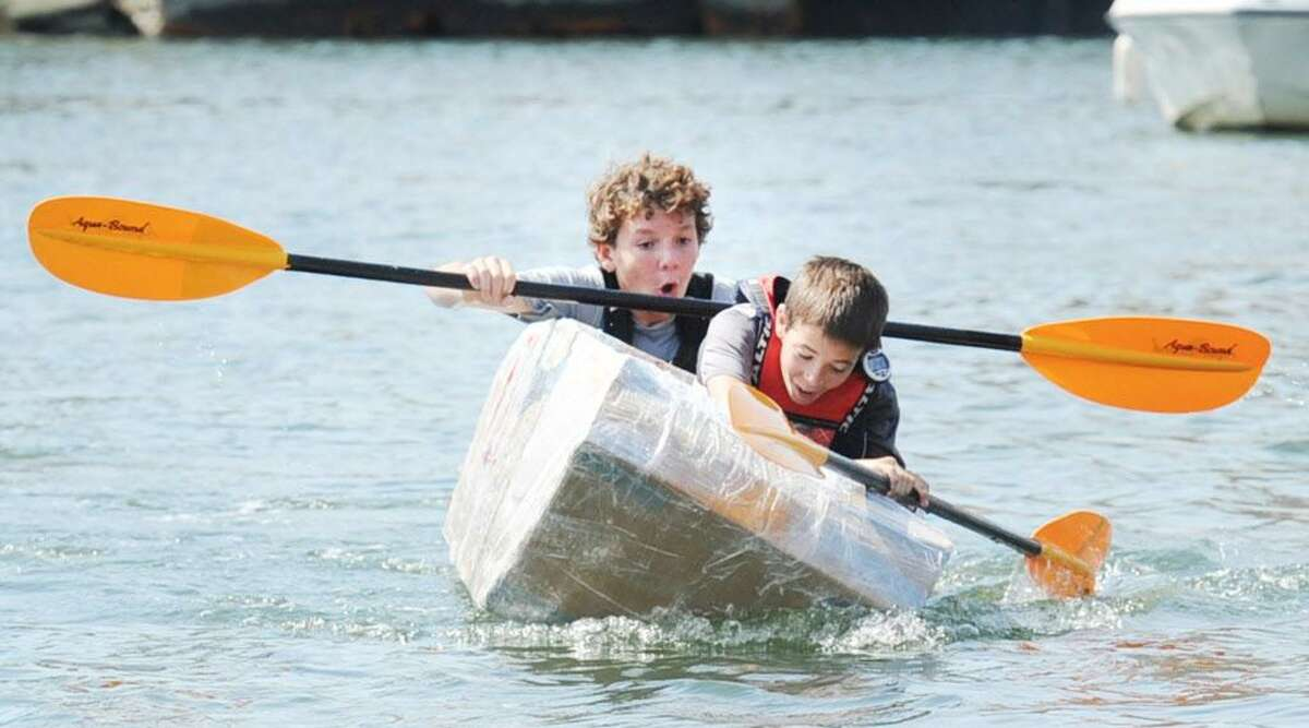 """The Stamford kayak """"Tribe"""" propelled by the duo of Griffin Gigliotti, front, and Angus Manion, had a precarious moment in which their Kayak almost sunk just before righting it and taking first place in the championship cardboard kayak race on Stamford Harbor during the SoundWaters HarborFest 16 at Harbor Point, Stamford, Conn., Saturday, Aug. 27, 2016."""