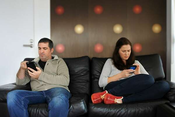 Couple (age 30 and 40) busy with their mobile phones are distracted by technology. Technology and relationship concept. Real people. Copy space
