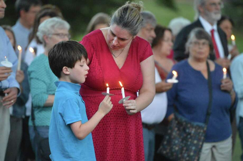 Staci Wilkes helps light her son Aaron's candle during an interfaith gathering Wednesday in Wilton, in response to the events in Charlottesville Va. Father Reggie Norman welcomed the community to the courtyard of the church to 'Standing Together, Standing Strong', a candlelight vigil at Our Lady of Fatima Church. Photo: Alex Von Kleydorff / Hearst Connecticut Media / Norwalk Hour