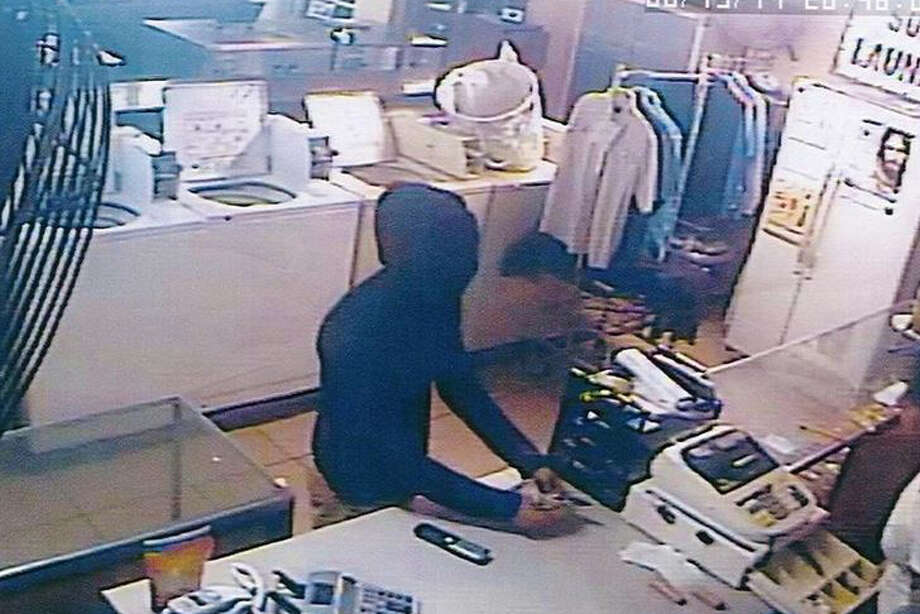 The robbery suspect is shown with his face covered, allegedly pointed a knife at the attendant.  Photo: Courtesy
