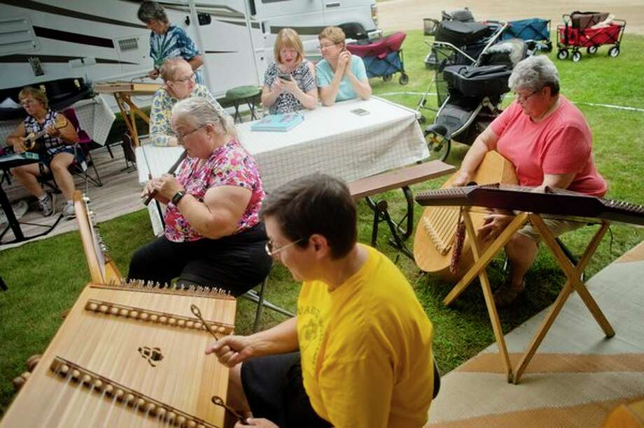 A group of people play folk songs together after arriving Monday at the Midland County Fairgrounds for the Midland Folk Festival. (Katy Kildee/kkildee@mdn.net)