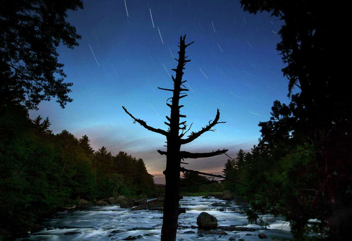 A dead spruce tree stands on the shore of the East Branch of the Penobscot River in this time exposure in the Katahdin Woods and Waters National Monument near Patten, Maine. Interior Secretary Ryan Zinke wants to retain the newly created Katahdin Woods and Waters National Monument in northern Maine, but said he might recommend adjustments to the White House on Thursday, Aug. 24, 2017.