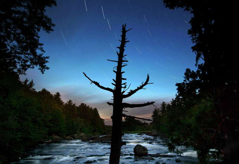A dead spruce tree stands on the shore of the East Branch of the Penobscot River in this time exposure in the Katahdin Woods and Waters National Monument near Patten, Maine. Interior Secretary Ryan Zinke wants to retain the newly created Katahdin Woods and Waters National Monument in northern Maine, but said he might recommend adjustments to the White House on Thursday, Aug. 24, 2017. Photo: Robert F. Bukaty, AP / Copyright 2017 The Associated Press. All rights reserved.