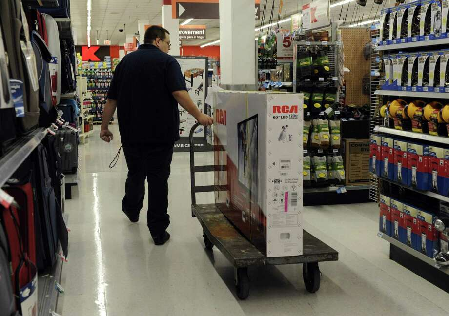 A store employee handles a large flat screen TV for a customer at Kmart in Southbury on Thanksgiving morning 2013. The store will close this year, one of 28 more announced on Thursday nationwide. Photo: Carol Kaliff / Carol Kaliff / The News-Times