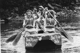 A young paddler winces with a final burst of energy as he and his teammates near the finish line in the raft race. The race, sponsored by Midland Jaycees for Holiday 1977, meandered about two miles down the river to Emerson Park. July 1977